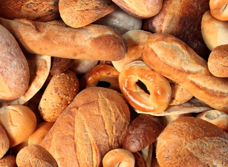 Photo for Bread background staple food concept with a group of baked goods from a bakery or home cooking made from whole wheat and grains with breads as pumpernickel pita focaccia bagel made from dough  - Royalty Free Image