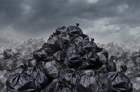 Foto de Garage dump concept with mountains of black waste bags of trash with an unpleasant smell  in an infinite landfill heap landscape as a background of environmental damage issues on a foggy  dark cloudy scene  - Imagen libre de derechos