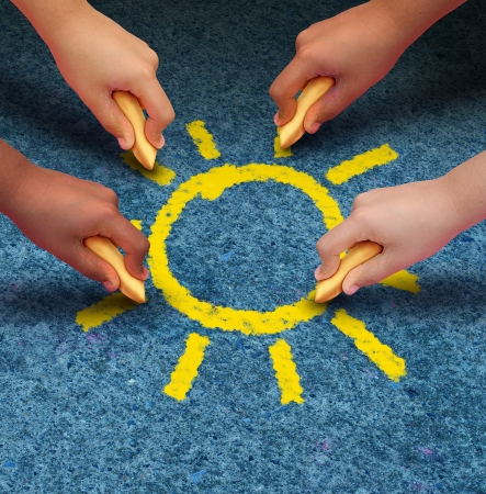 Photo for Community education and children learning and development concept with a group of hands representing ethnic groups of young people holding chalk cooperating together to draw a yellow sun shape as a metaphore for friendship  - Royalty Free Image