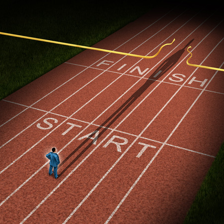 Photo pour Forward thinking business concept for success acceleration with a businessman standing on the start line in a track and feild path with a cast shadow breaking through the finish line ribbon for victory  - image libre de droit