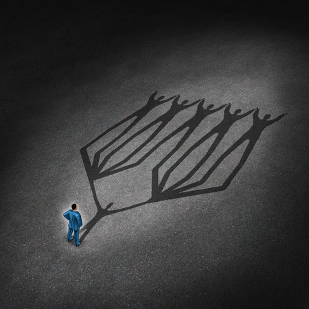 Photo pour Team leadership and business leader concept with a businessman standing with a cast shadow of a connected network group of employees and working partners as a metaphor for successful teamwork partnership   - image libre de droit