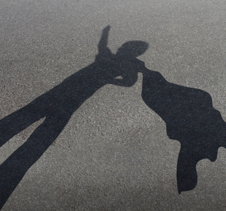 Photo pour Superhero kid pretending to be a powerful courageous hero with a cape flying in the wind as a fun childhood play symbol for the fertile imagination of a child as a cast shadow on an urban asphalt road  - image libre de droit