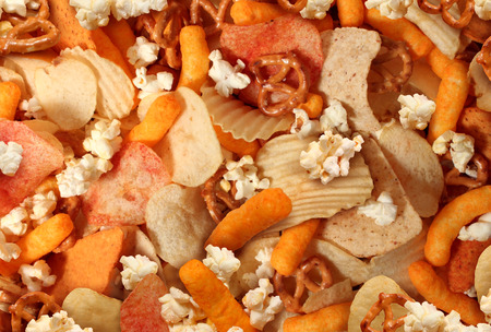 Photo pour Snacks background with salty crunchy treats as potato chips and cheese flavored puffs fried or baked food as pretzels pop corn and nachos as a symbol of assorted party mix appetizer  - image libre de droit