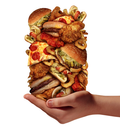 Photo for Over eating and compulsive indulgence of fast food concept as a hand holding up a huge stack of junk food as hamburgers hotdogs and french fries as an unhealthy diet nd bad nutrition symbol isolated on a white background  - Royalty Free Image