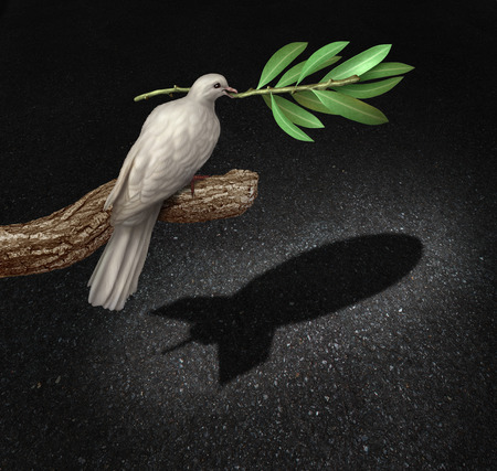 Photo for Risk of war concept as a freedom peace dove holding an olive branch casting a shadow that is shaped as a bomb as a symbol of  the danger of warfare caused by hatred and political posturing. - Royalty Free Image