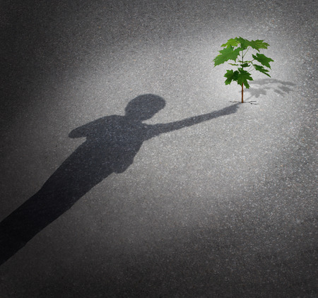Photo pour Grow concept with a shadow of a child touching a tree sapling growing through city pavement as a symbol for the future environment protection and the support of the next generation - image libre de droit
