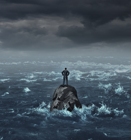 Foto de Stranded businessman lost at sea standing on an isolated rock as a business concept for financial despair or being lost and needing career or financial help to escape the crisis - Imagen libre de derechos
