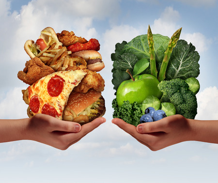 Foto de Nutrition choice and diet decision concept and eating choices dilemma between healthy good fresh fruit and vegetables or greasy cholesterol rich fast food with two hands holding food trying to decide what to eat. - Imagen libre de derechos