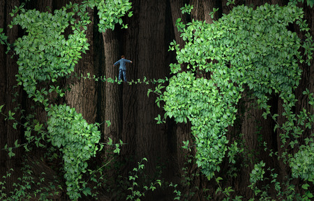 Global growth risk business concept as a businessman walking on a tightrope made from plant vines in a background of forest tree leaf vine shaped as a world map as a metaphor for international trade and investing uncertainty or environment conservation is