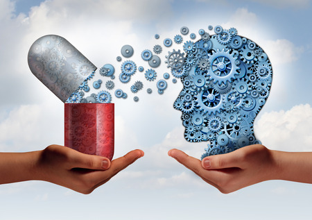 Foto de Brain medicine mental health care concept as hands holding an open pill capsule releasing gears to a human head made of machine cog wheels as a symbol for the pharmaceutical science of neurology and the treatment of psychological illness. - Imagen libre de derechos