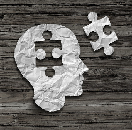 Foto de Puzzle head brain concept as a human face profile made from crumpled white paper with a jigsaw piece cut out on a rustic old wood background as a mental health symbol. - Imagen libre de derechos
