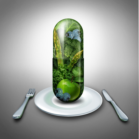 Foto de Food supplement concept as a giant pill or medicine capsule with fresh fruit and vegetables inside on a table place setting  - Imagen libre de derechos