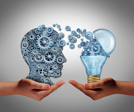 Foto de Concept of creating ideas and achievement symbol of aspiration success as two hands holding a group of connected gears shaped as a human head and an open lightbulb as an icon of imagination and innovation. - Imagen libre de derechos