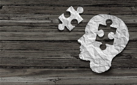 Foto de Mental health symbol Puzzle and head brain concept as a human face profile made from crumpled white paper with a jigsaw piece cut out on a rustic old double page spread horizontal wood background. - Imagen libre de derechos