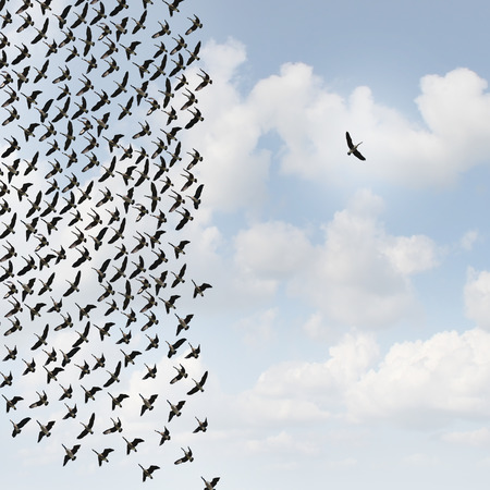Foto de Independent thinker concept and new leadership concept or individuality as a group of flying geese with one individual bird going in the opposite direction as a business symbol for innovative thinking and as a different nonconformist maverick. - Imagen libre de derechos