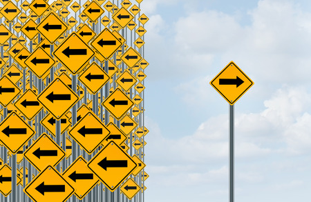 Photo pour Direction individuality and independent thinking concept as a group of directional arrow traffic signs with one individual pointing in the opposite way as a business icon for innovative solution. - image libre de droit