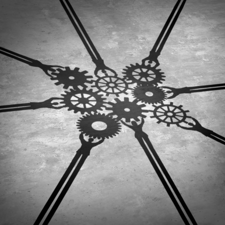 Foto de People teamwork holding gears connected together as a social community group symbol or business concept working for a common cause with cast shadows holding a cogwheel network in a corporate team partnership. - Imagen libre de derechos