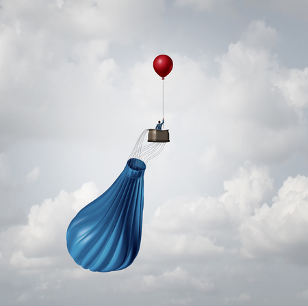 Foto de Emergency business plan and crisis management strategy metaphor as a businessman in a broken deflated hot air balloon being saved by a single small red party balloon as an innovative response solution idea. - Imagen libre de derechos