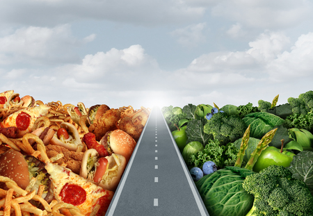 Photo pour Diet lifestyle concept or nutrition decision symbol and food choices dilemma between healthy good fresh fruit and vegetables or greasy cholesterol rich fast food with a road or path between leading to a light. - image libre de droit