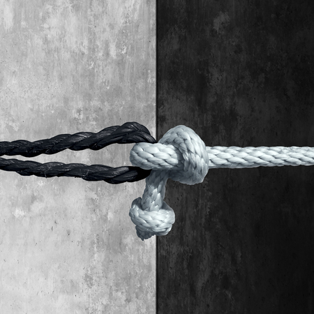 Foto de Racial unity concept as a symbol against racism in society as a white and black rope tied together as a metaphor for friendship and respect. - Imagen libre de derechos