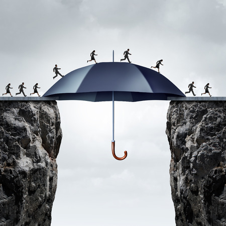 Foto de Security bridge concept as business people running across two high cliffs with the help of a safe giant umbrella bridging the gap. - Imagen libre de derechos