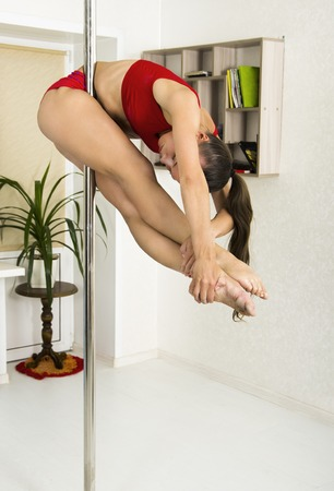 Foto per A girl in a red tracksuit is engaged on the pylon at home. Shooting in the white room. - Immagine Royalty Free