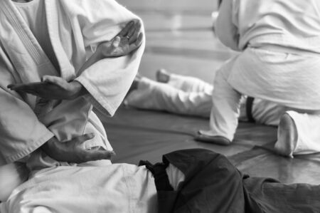 Photo pour Black and white image of aikido. Hands of fighters. The traditional form of clothing in Aikido. Background image. No faces and recognizable elements - image libre de droit