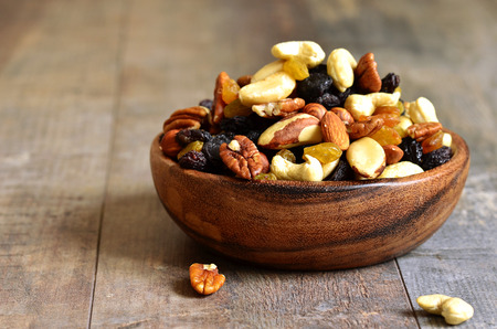 Photo for Dried fruits and nuts mix in a wooden bowl. - Royalty Free Image