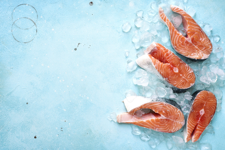Photo for Steaks of raw salmon on ice on a blue slate,stone or metal background.Top view with space for text. - Royalty Free Image