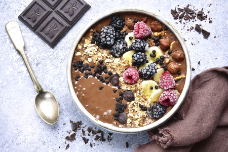 Photo for Chocolate banana smoothie bowl with frozen berries and granola on a light grey slate, stone or concrete background.Top view. - Royalty Free Image
