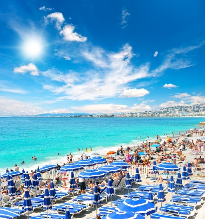 Photo for View of the beach in Nice, France, near the Promenade des Anglais, full with tourists, sunbeds and umbrellas on summer hot day - Royalty Free Image