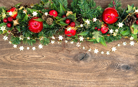 Foto de christmas decorations garland with red apple and green pine branches over wooden background - Imagen libre de derechos
