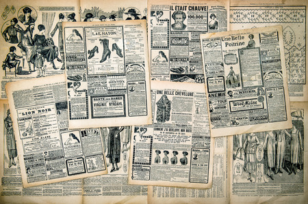 Foto de Newspaper pages with antique advertising. Woman - Imagen libre de derechos