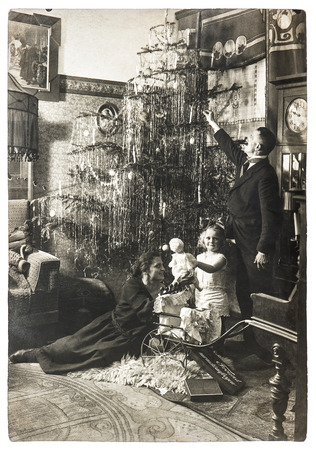 Photo pour vintage family portrait of parents and child with christmas tree. antique picture with original film grain and blur. black and white photo - image libre de droit