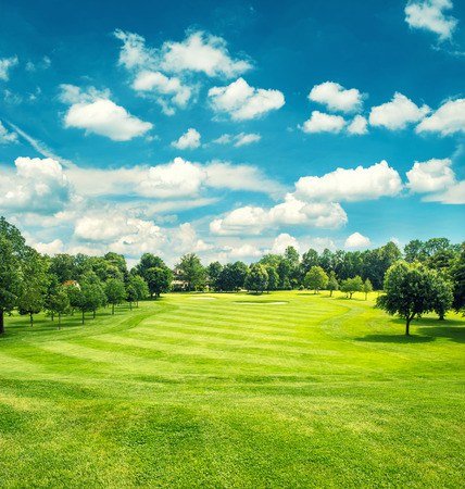 Foto de Golf field and blue cloudy sky. Beautiful landscape with green grass. Retro style toned picture - Imagen libre de derechos