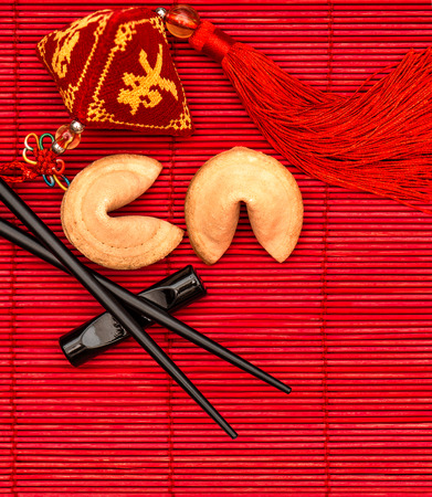 Foto de Lucky charm, fortune cookies and chopsticks. Chinese new year red background - Imagen libre de derechos