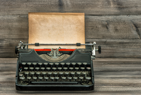 Photo pour Antique typewriter with old textured paper page on wooden table. Vintage style toned picture - image libre de droit