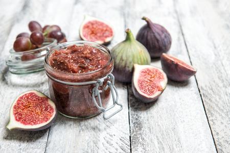 Foto de Figs jam in jar. Fruit marmalade on rustic wooden background - Imagen libre de derechos
