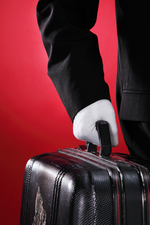 Photo pour Hotel porter carrying suitcase, close up, side view - image libre de droit