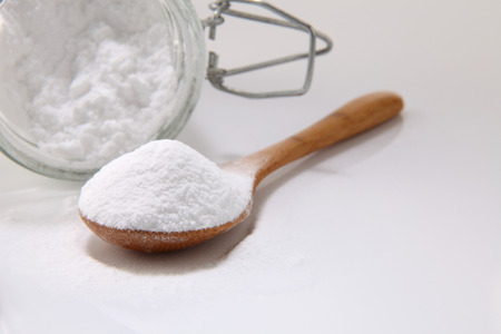Photo for wooden spoon full of baking soda on the white background - Royalty Free Image