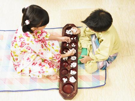 Foto de a boy and girl playing traditional congkak - Imagen libre de derechos