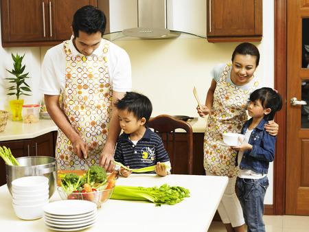 Foto de Family cooking in the kitchen together - Imagen libre de derechos