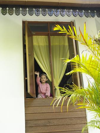 little boy waiving hand behind of window panel