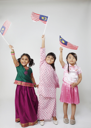 Photo pour Full lenght of three kids holding flag - image libre de droit