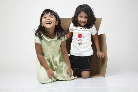 Photo for Two little girls coming out from the box - Royalty Free Image