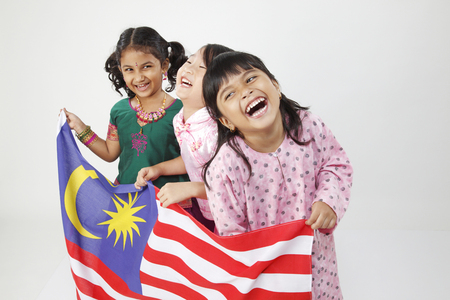 Foto de Three girls holding flag, laughing - Imagen libre de derechos