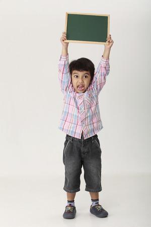 Photo pour boy holding a blank black board - image libre de droit