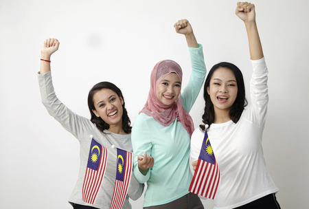 Photo pour three multi racial malaysian holding flag wtih raised arm - image libre de droit