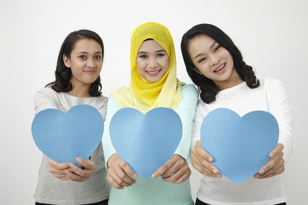 Photo for three multi racial malaysian holding heart shape cardboard looking at camera - Royalty Free Image