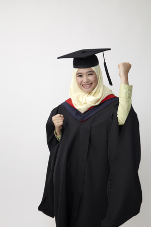 Photo for Happy young women in mortarboard  isolated on white - Royalty Free Image